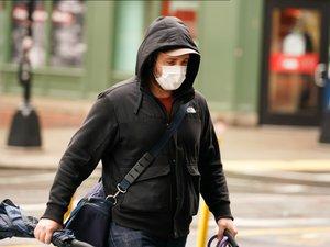 Un piéton portant un masque de protection contre le Coronavirus