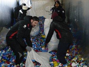 """Les joueurs de Rouen en train de décharger des cargaisons de bouchons à recycler, dans le cadre de l'opération menée avec l'association """"Bouchons 276""""."""