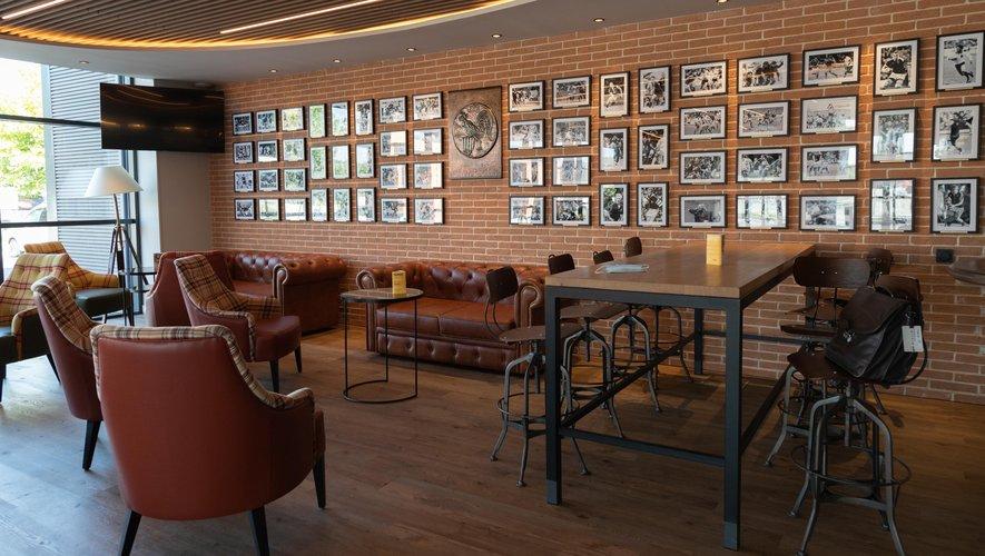 L'entrée de l'hôtel Twickenham Pub restaurant est garnie d'une soixantaine de portraits dédicacés de joueurs (à gauche). Guy Spanghero, le propriétaire entouré de ses fils Nicolas et Philippe, posent devant une statue de Casimir Ferrer (à droite).  Photos Stéphanie Biscaye